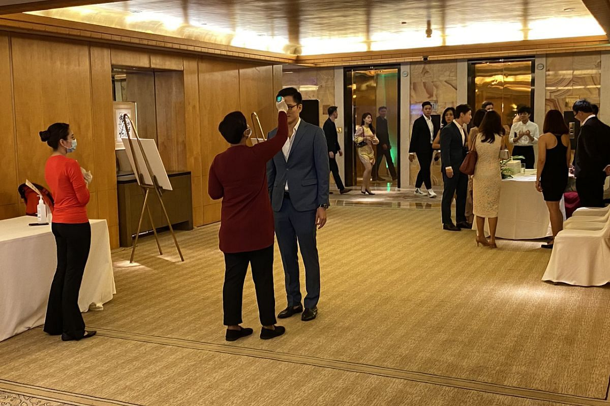 Guests at a wedding function at the The Ritz-Carlton, Millenia Singapore on March 21, 2020, getting their temperature taken before they are allowed into the function room.
