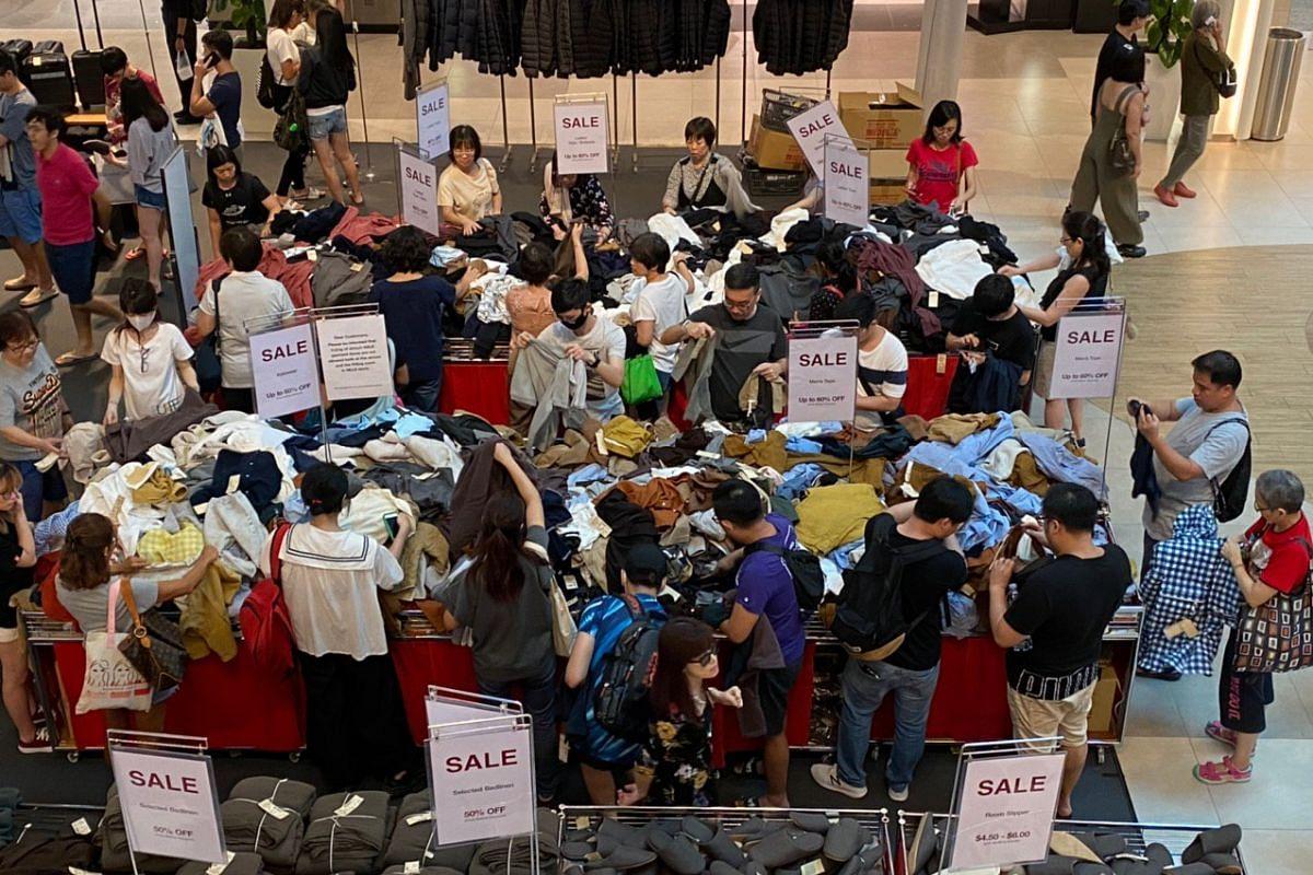 Shoppers rummaging through bargain bins at the atrium of Plaza Singapura on March 21, 2020.