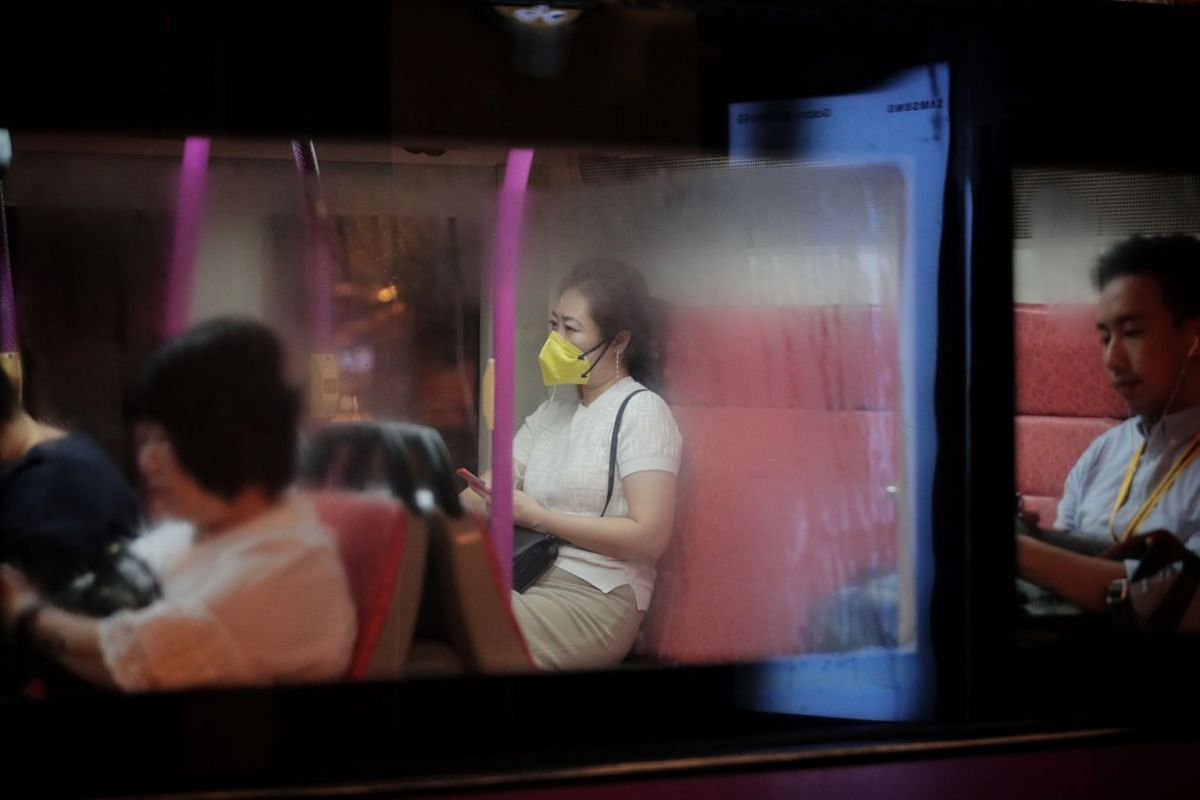 A commuter wearing mask is pictured through frosted windows on a bus at Tanglin Road on March 23, 2020.