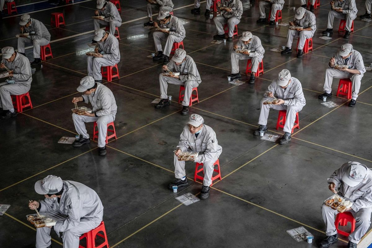 Employees have their lunch break at an auto plant of Dongfeng Honda in Wuhan on March 23, 2020.
