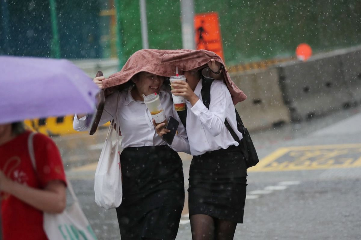 Pedestrians take cover from the rain at a traffic junction along North Bridge Road on March 23, 2020.