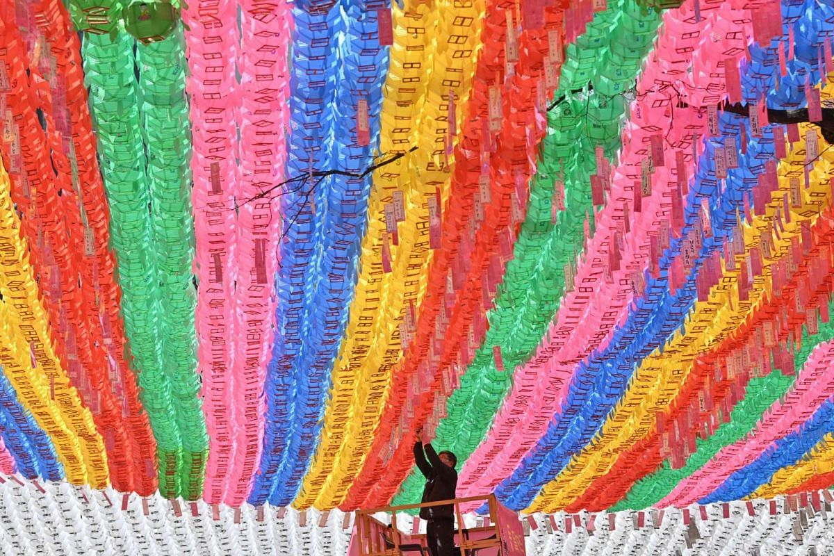 A temple worker attaches name cards with the wishes of Buddhist followers to lotus lanterns ahead of Buddha's birthday at Jogyesa Temple in Seoul on March 23, 2020.