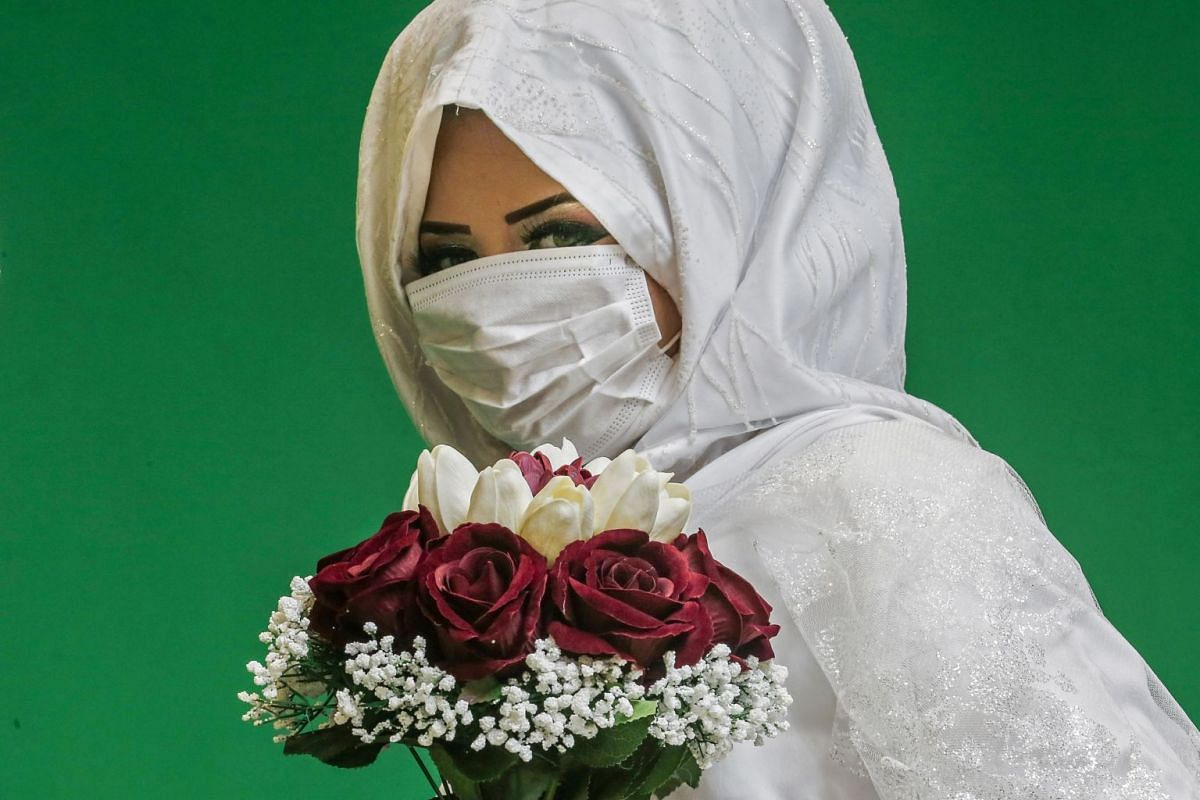 Palestinian bride Israa poses for pictures at a local studio while wearing a face mask before her wedding ceremony in Khan Yunis in the southern Gaza Strip on March 23, 2020.