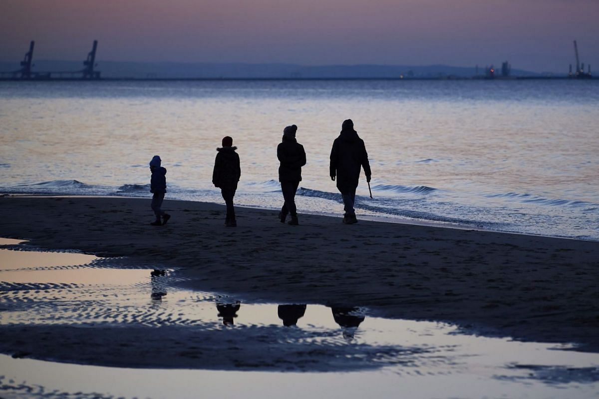 A family walks by the sea in Gdansk, Poland, on March 24, 2020.