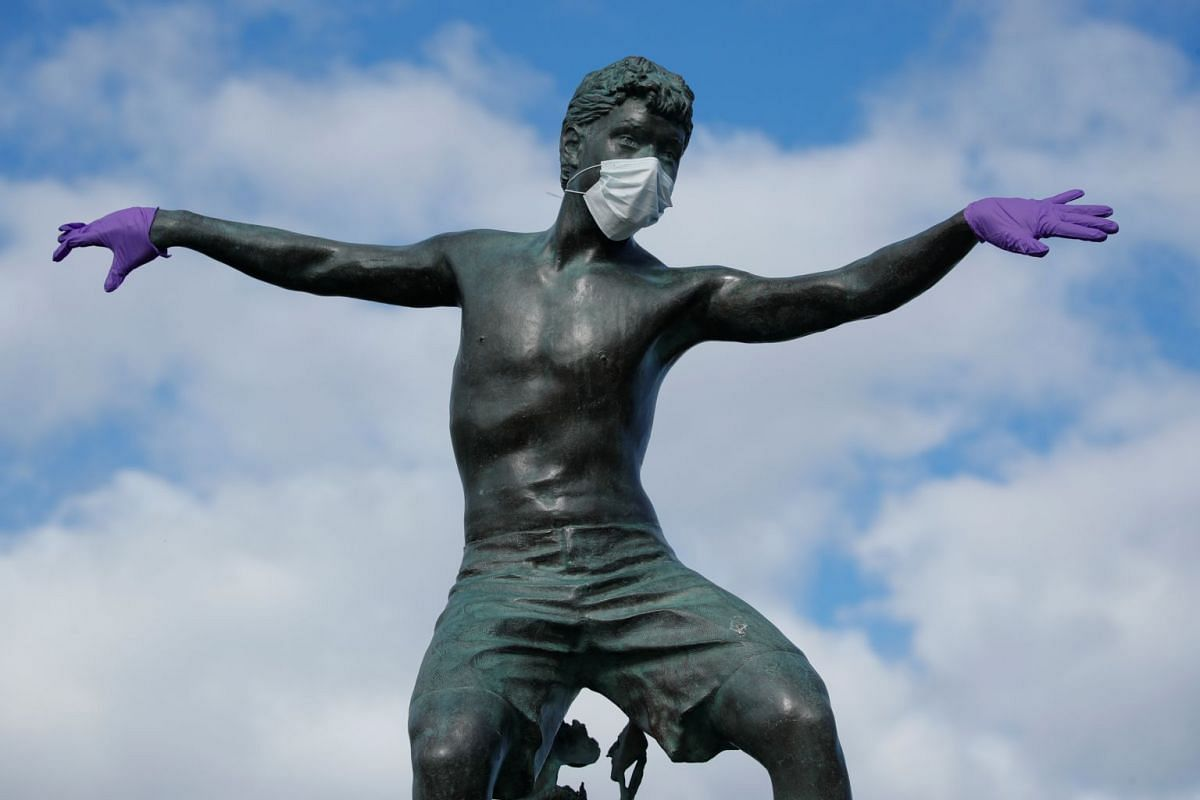 A surfer statue along the beach is decorated by pranksters with a mask and gloves in Encinitas, California, on March 24, 2020.