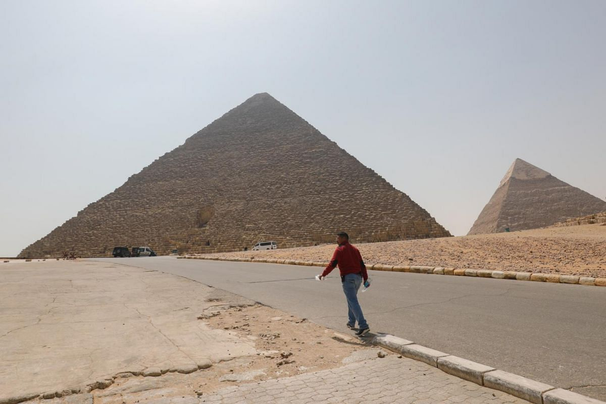 A man walks past the Great Pyramids in Giza, on the outskirts of Cairo, Egypt, on March 25, 2020.