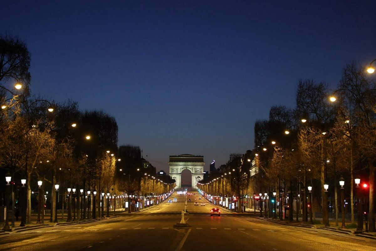 A photo of an empty Champs-Elysees Avenue and the Arc de Triomphe at night in Paris, on March 24, 2020.