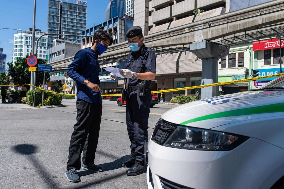A policeman checks a man's travel documents in Kuala Lumpur, on March 25, 2020. Malaysia's nationwide movement restrictions have been extended from March 31 to April 14.