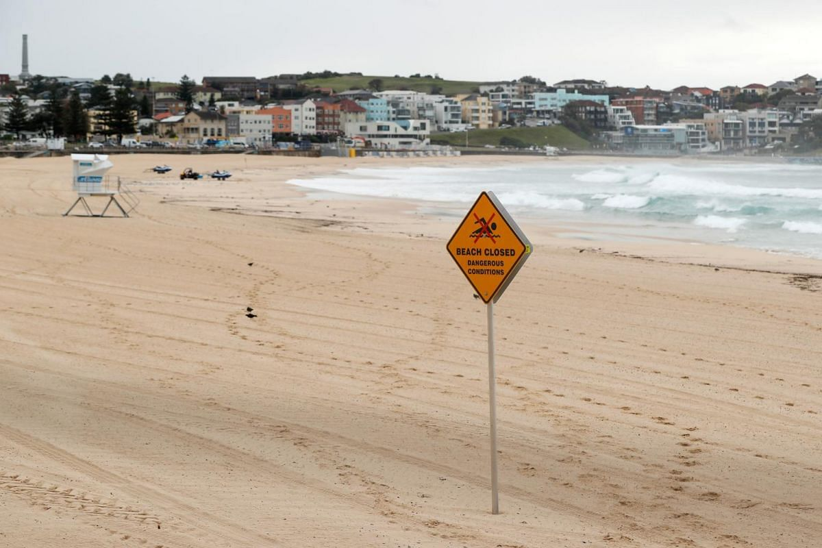 """A 'Beach Closed"""" sign displayed at an empty Bondi Beach in Sydney, on March 24, 2020."""