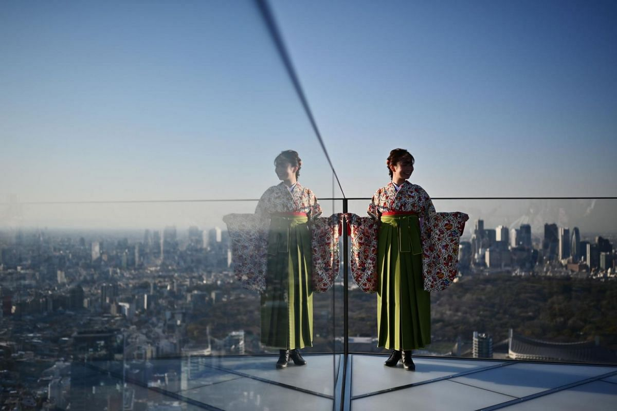 A woman poses for a photo in a highrise viewing area on a skyscraper in Tokyo, Japan, on March 25, 2020.