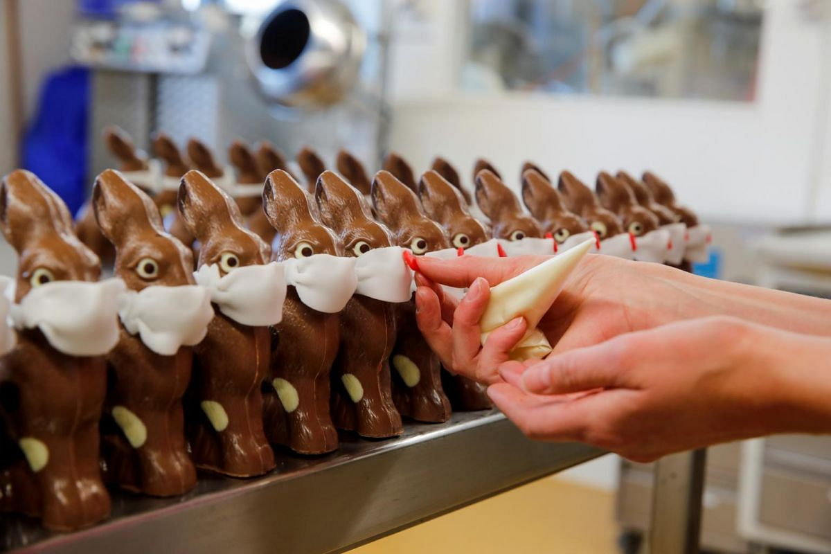 An employee prepares chocolate Easter bunnies wearing protective masks at Baeckerei Bohnenblust bakery in Bern, Switzerland, on March 25, 2020.