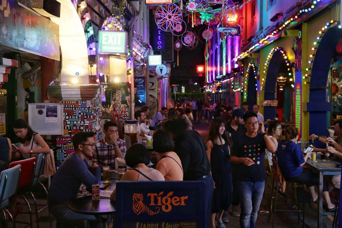 Customers in Haji Lane at 10.10pm on March 26, 2020, before the 11.59pm deadline for bars and other entertainment venues, including nightclubs and karaoke outlets, to close until April 30. PHOTO: THE STRAITS TIMES/KEVIN LIM
