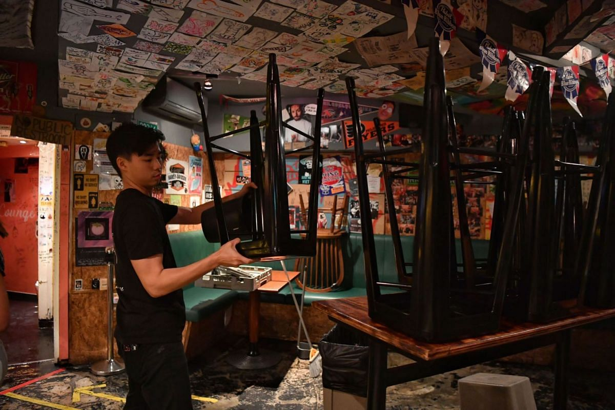 Staff at Skinny's Lounge in Boat Quay started cleaning up and getting ready to shut down at about 11.30pm on March 26, 2020, before the 11.59pm deadline for bars and other entertainment venues, including nightclubs and karaoke outlets, to close unt