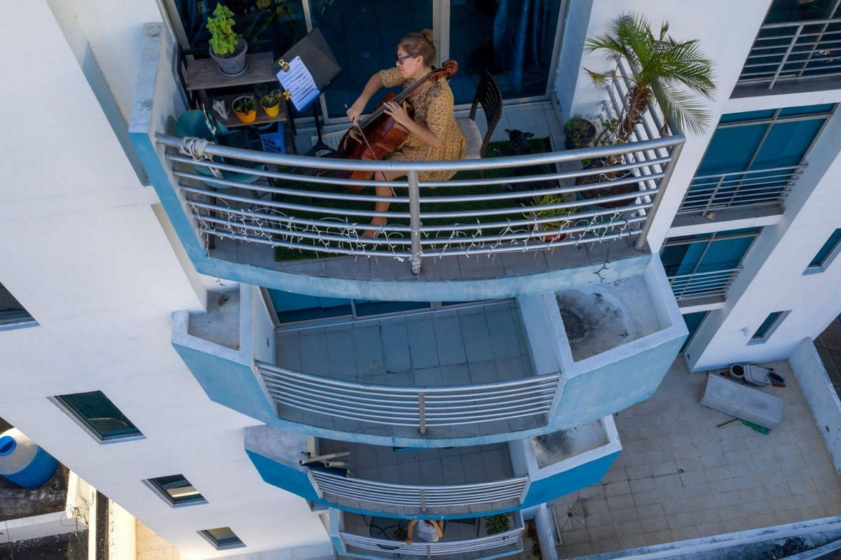A photo issued on March 25, 2020, shows Uruguayan cellist Karina Nunez playing on the balcony of her apartment in Panama City on March 23, 2020 , during the mandatory isolation from 5pm to 5am as a preventive measure against the spread of the COVID-1