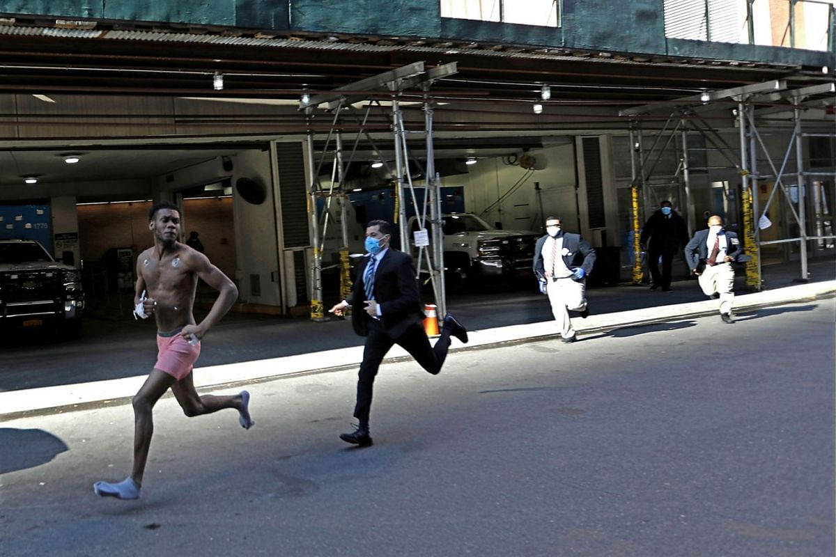 An unidentified person, with apparent remnants of medical treatment on him, runs out of the Emergency room and is chased by hospital security at 58th St. by Mount Sinai West Hospital, in New York, New York, USA, on 26 March 2020. PHOTO: EPA-EFE