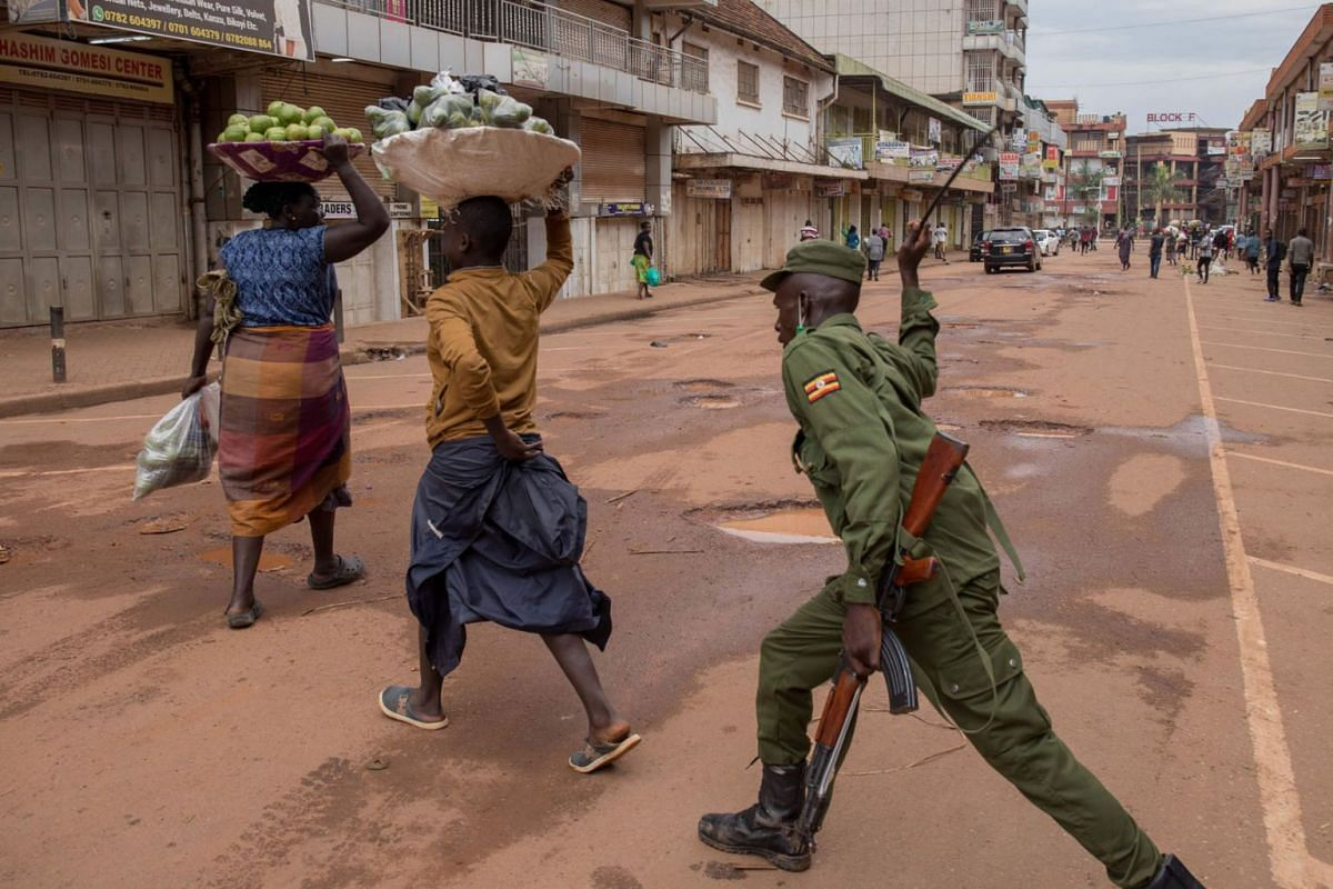 A police officer beats a female orange vendor on a street in Kampala, Uganda, on March 26, 2020, after Ugandan President Yoweri Museveni directed the public to stay home for 32 days starting March 22, 2020 to curb the spread of the COVID-19 coronavir
