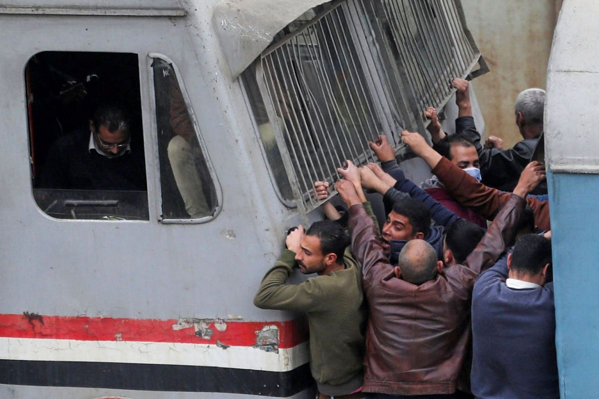 People travel on an overcrowded train before hours of curfew which was ordered by the Egyptian Prime Minister Mostafa Madbouly to contain the spread of the coronavirus disease (COVID-19), on the outskirts of Cairo, Egypt March 26, 2020. PHOTO: REUTER