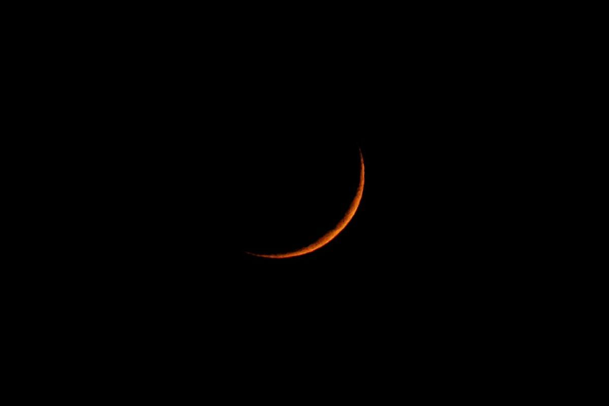A waxing crescent moon is seen over the skies of Harpenden, Britain, on March 26, 2020. REUTERS