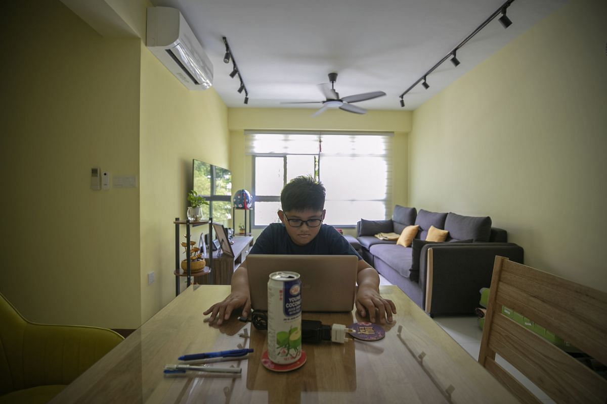 Primary 4 student from Marsiling Primary School Keshawn Cleve Ong, 10, does home-based learning in the living room of a HDB flat in Choa Chu Kang. A Malaysian, his family stays in Johor Baru and commutes daily to Singapore together with his father, w