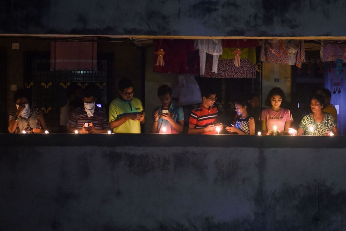Residents light candles and turn on their mobile phone lights in their balcony to observe a nine-minute vigil called by India's Prime Minister in a show of unity and solidarity in the fight against the coronavirus pandemic in Mumbai on April 5, 2020.