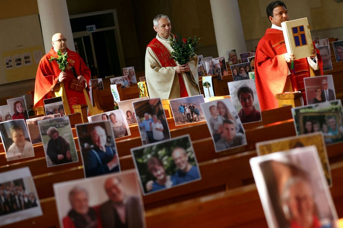 Priest Joachim Giesler holds a mass with photos of believers who were asked to send in pictures after the service was closed due to the spread of coronavirus disease (COVID-19) in Achern, Germany, April 5, 2020. PHOTO: REUTERS