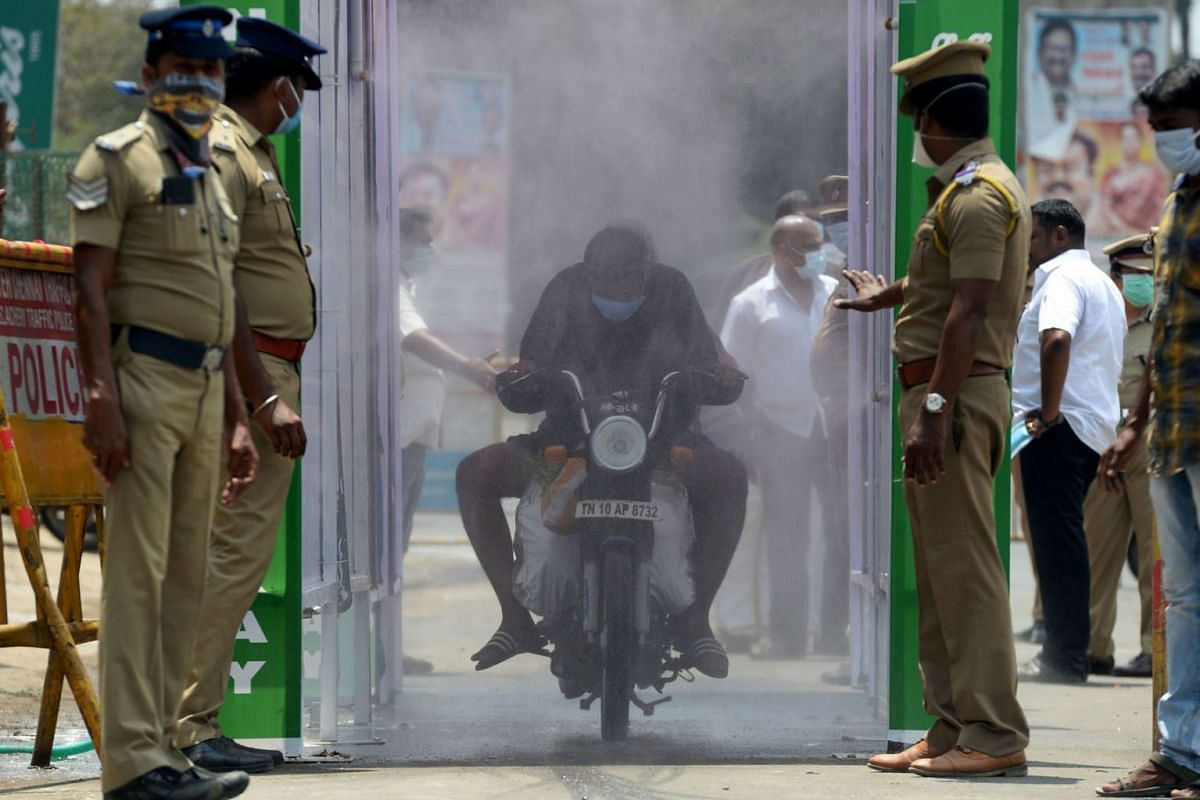 A motorist rides through a disinfection tunnel during a government-imposed nationwide lockdown as a preventive measure against the COVID-19 coronavirus in Chennai on April 5, 2020. PHOTO: AFP