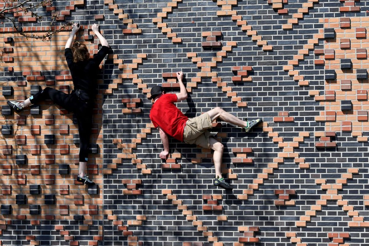 Climbers Carlotta and Rafael train on a house wall in Hafencity district, as the spread of coronavirus disease (COVID-19) continues in Hamburg, Germany, April 5, 2020. PHOTO: REUTERS