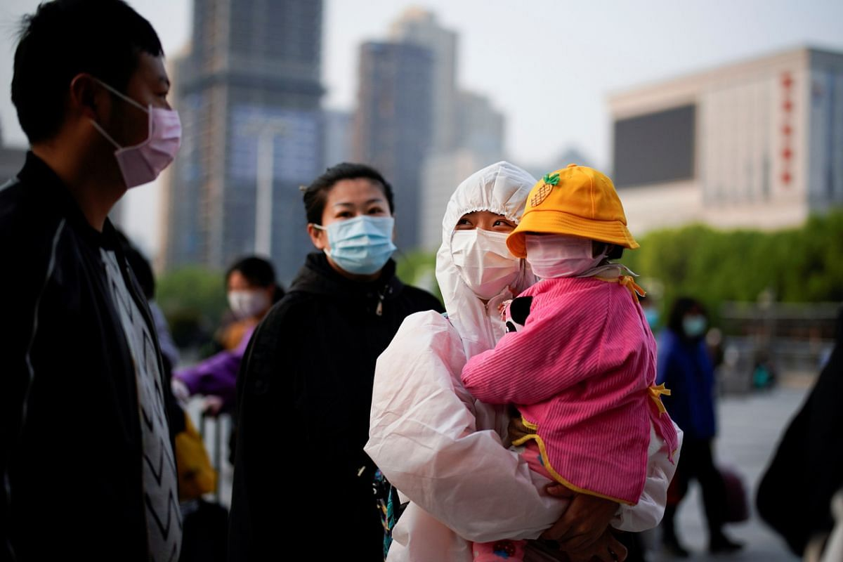 People wearing face masks and protective suits at Wuhan's Hankou Railway Station, on April 8, 2020.