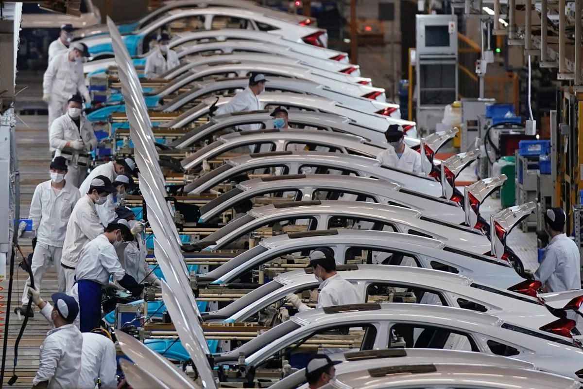 Employees work on a production line inside a Dongfeng Honda factory in Wuhan on April 8, 2020.