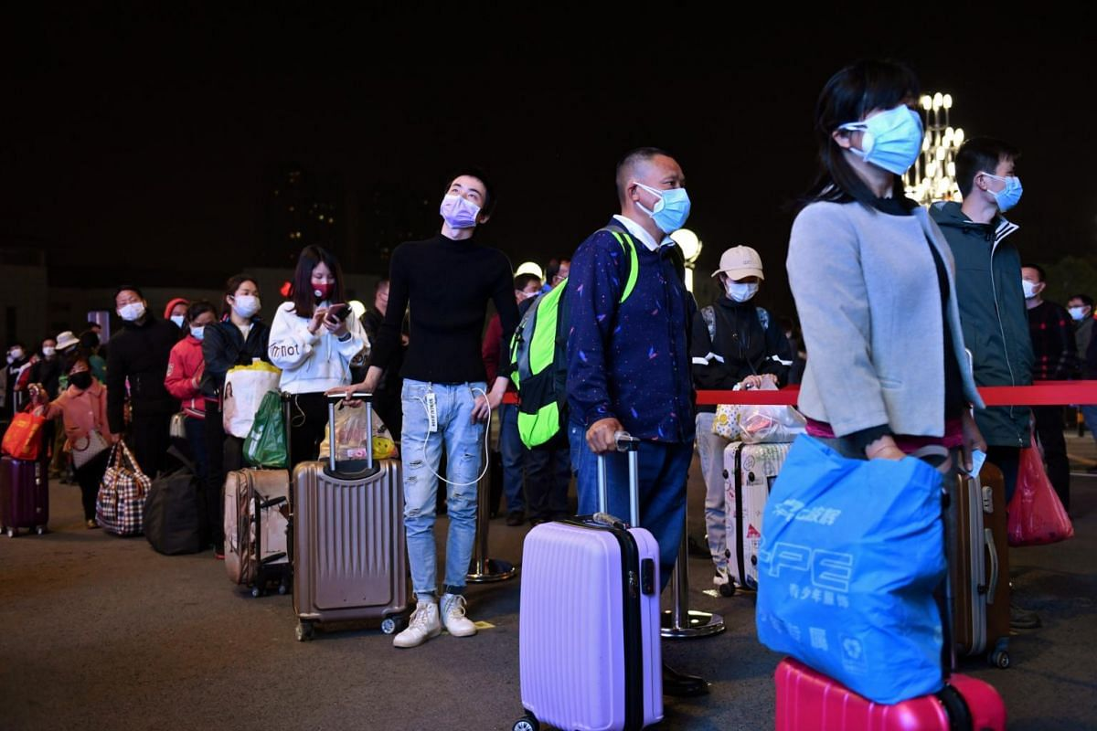 Travellers line up with their belongings outside Wuchang Railway Station before travel restrictions to leave Wuhan were lifted, on April 7, 2020.