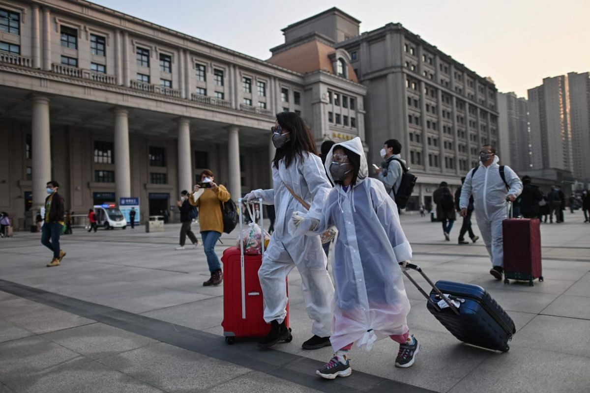 People wearing protective clothing and masks arrive at Hankou Railway Station in Wuhan to board one of the first trains leaving the city on April 8, 2020.