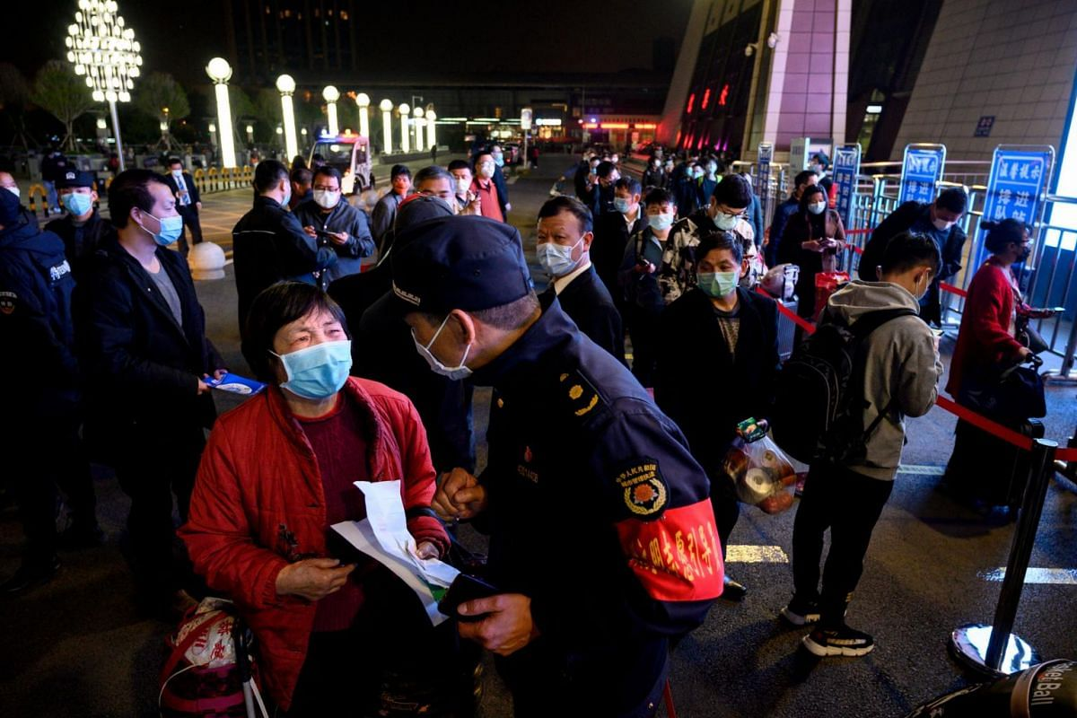 Passengers wear masks as they form a queue at the Wuchang Railway Station in Wuhan, early on April 8, 2020.