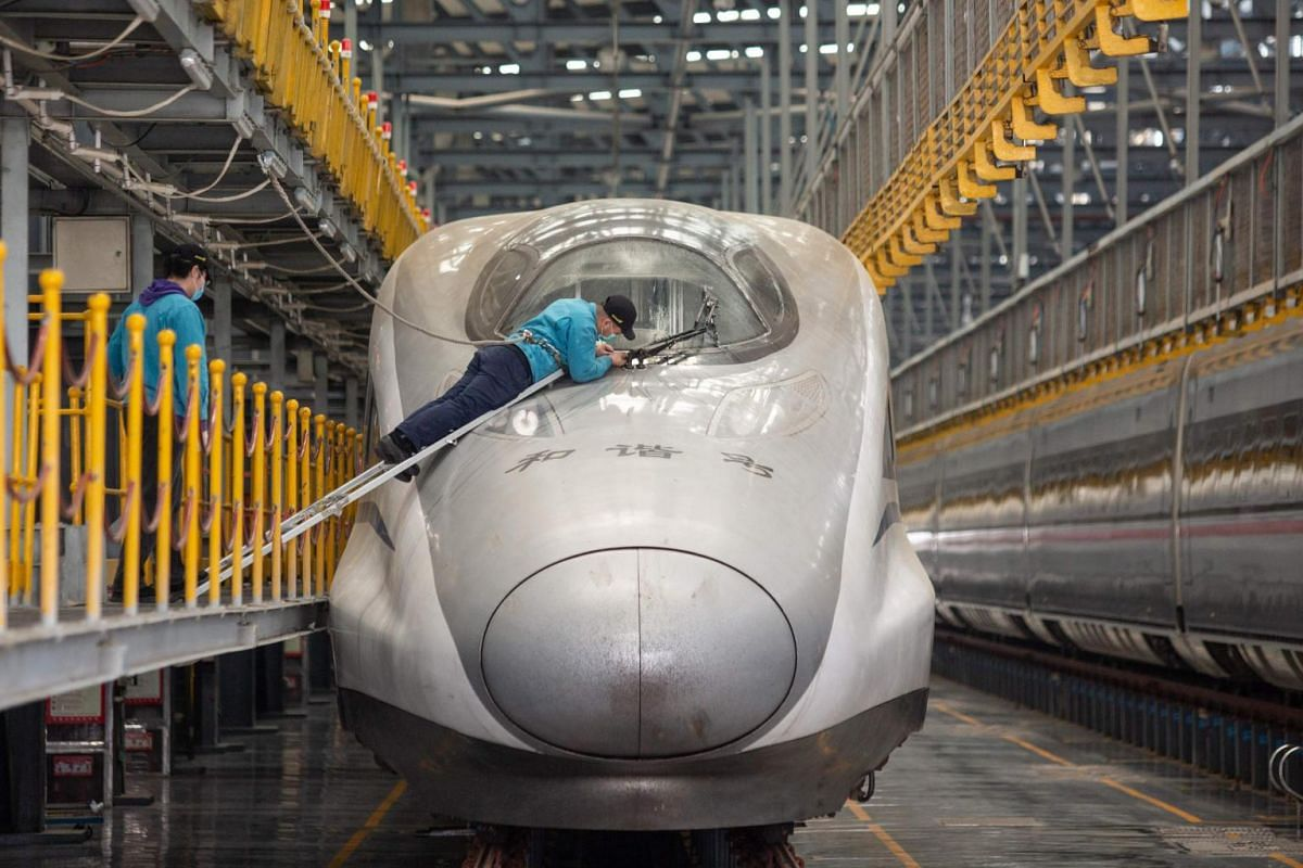 A staff member checks on a bullet train in preparation for resuming operations in Wuhan on April 7, 2020.