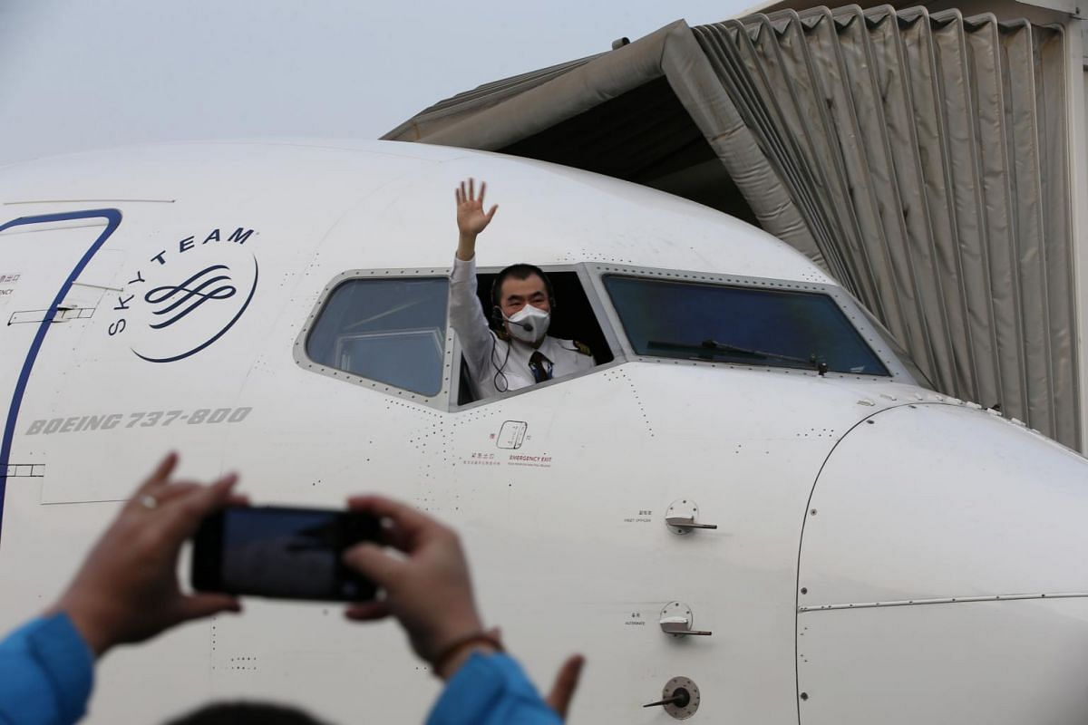 A pilot leans out of the cockpit window to wave goodbye before the China Eastern airlines flight, the first domestic flight from Wuhan that resumed service after travel restrictions were lifted, takes off from Wuhan Tianhe International Airport to Sa