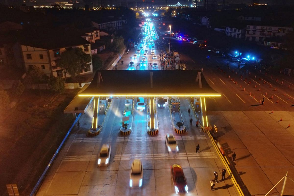 Vehicles travel through a toll station of an expressway moments after travel restrictions to leave Wuhan were lifted, early on April 8, 2020.