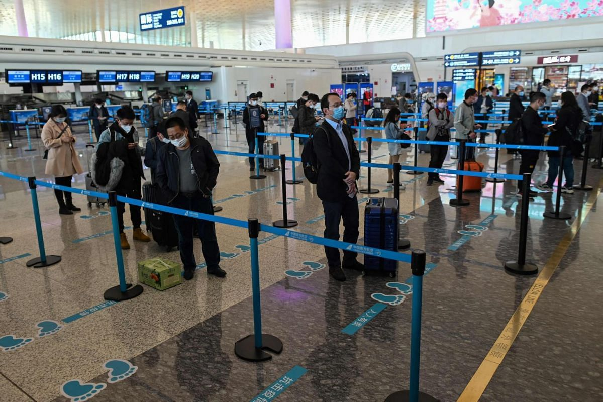 Passengers wearing protective gear receive their tickets at the airport in Wuhan on April 8, 2020.