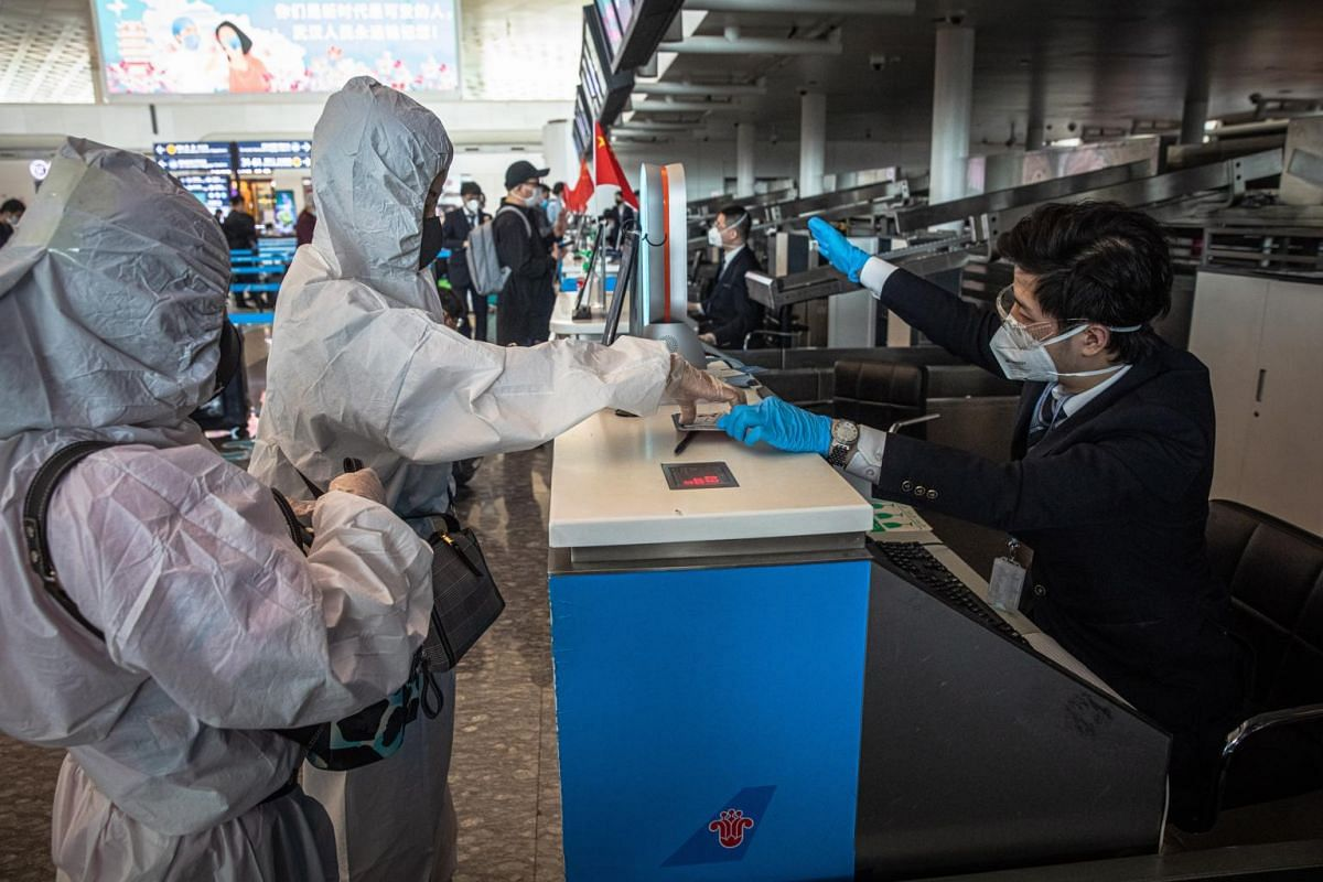 Passengers wearing protective gears receive their tickets at the airport after the lockdown was lifted in Wuhan, China, on April 8, 2020.