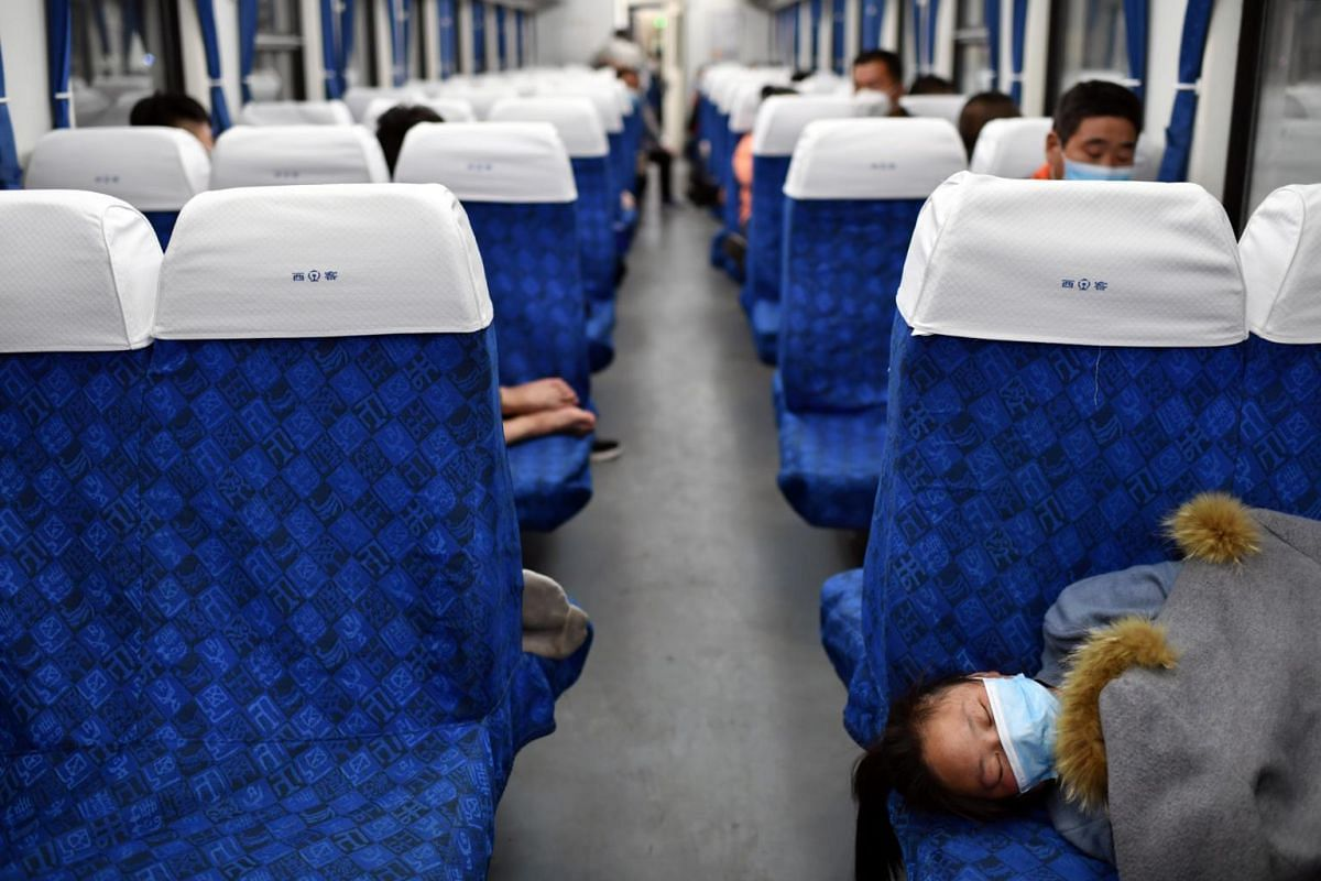 Passengers rest inside a high speed train at Wuchang Railway Station in Wuhan on April 8, 2020.