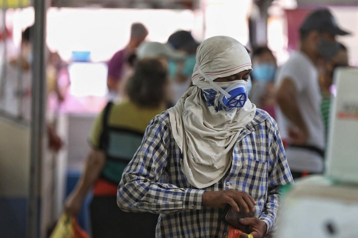 A masked up man in a wet market at 17 Old Airport Road on April 12, 2020.