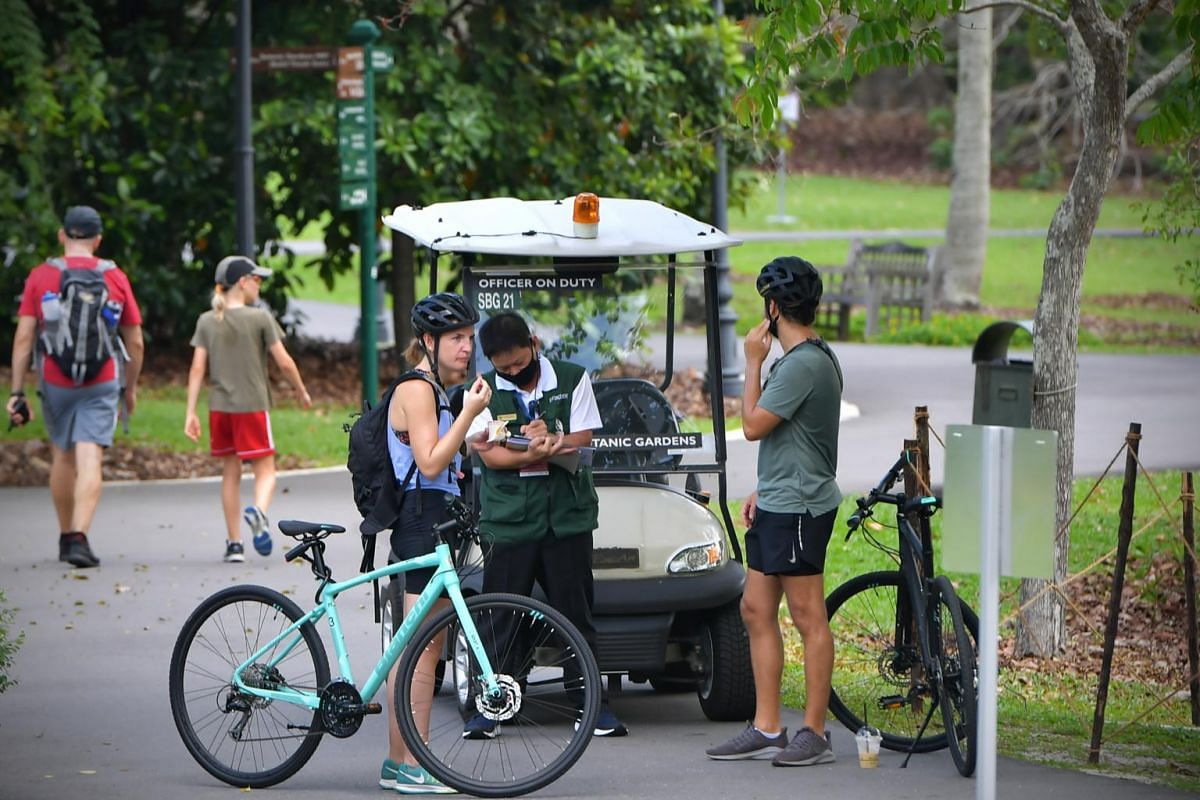 A National Parks Board officer stops cyclists who flouted circuit breaker measures at the Singapore Botanic Gardens on April 12, 2020.