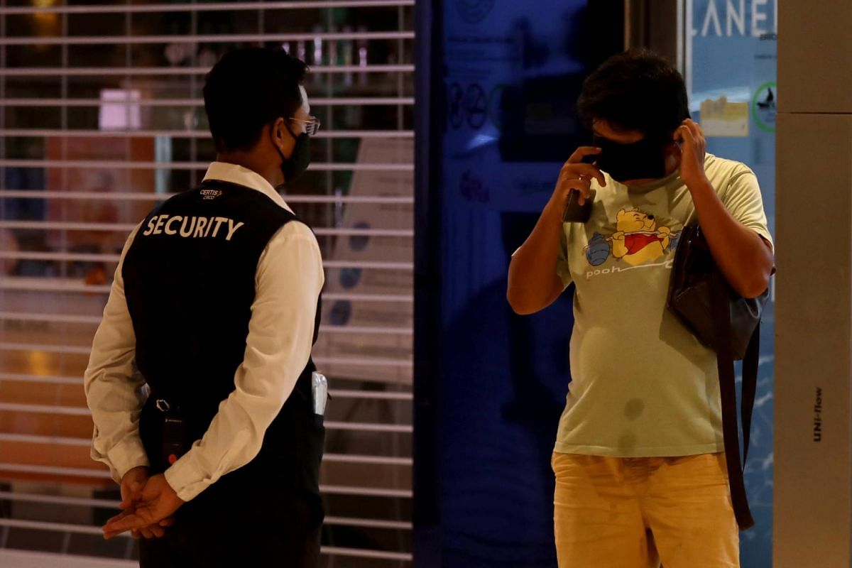 A man is made to put on a mask by a security officer before entering Bedok Mall on April 12, 2020.