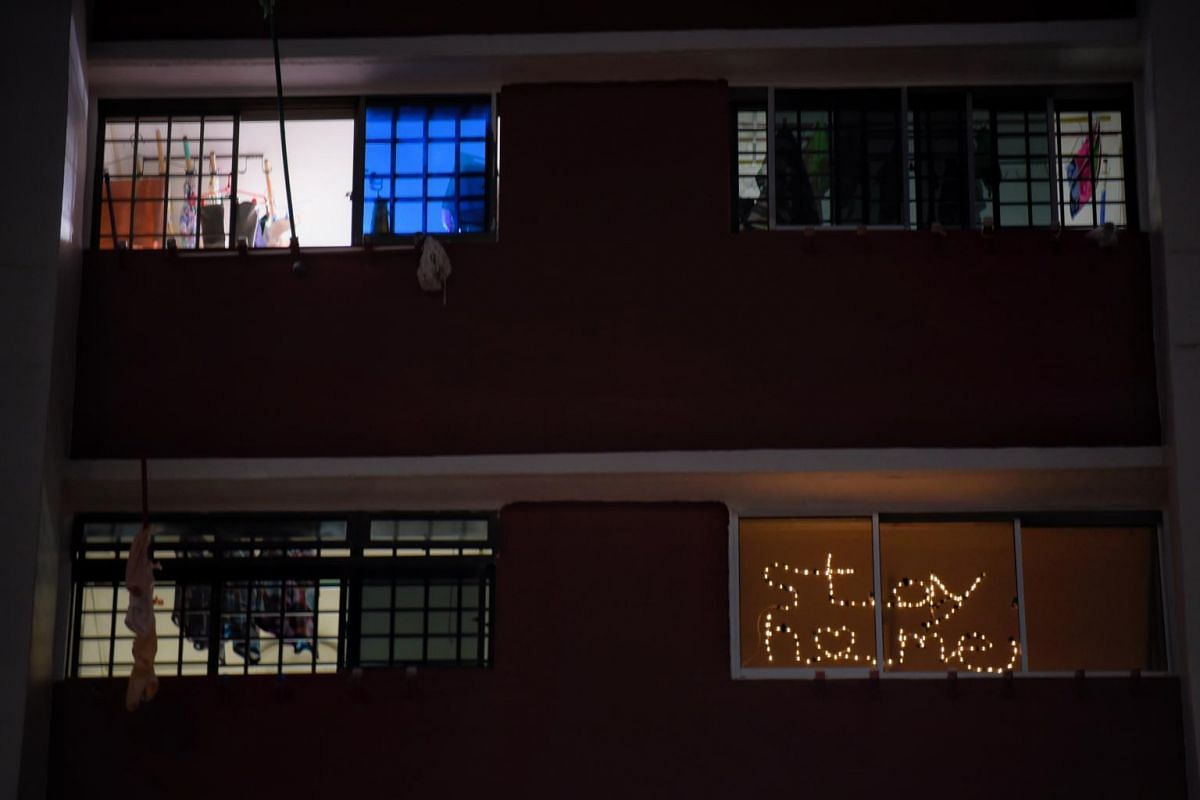 """The words """"Stay Home"""" formed on the window of Christopher Cheah and his wife Joyce Tan's Hougang apartment on April 11, 2020."""