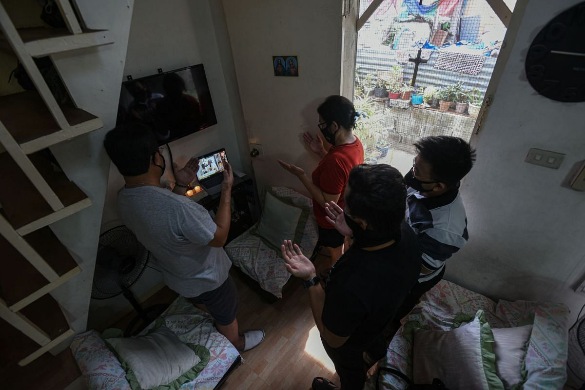 Catholic worshippers in an urban community on the outskirts of Manila attend a mass via online live streaming during Easter Sunday on April 12, 2020.