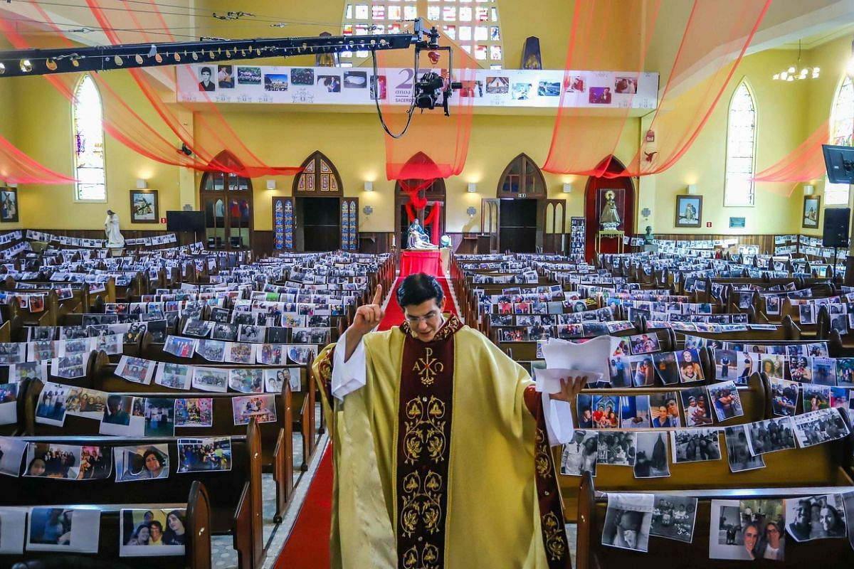 Priest Reginaldo Manzotti, of the Nossa Senhora de Guadalupe sanctuary in Curitiba, Brazil, streams his Easter Sunday service on April 12, 2020, with printed photos of his congregation in the pews as his parishioners self-isolate during the coronavir