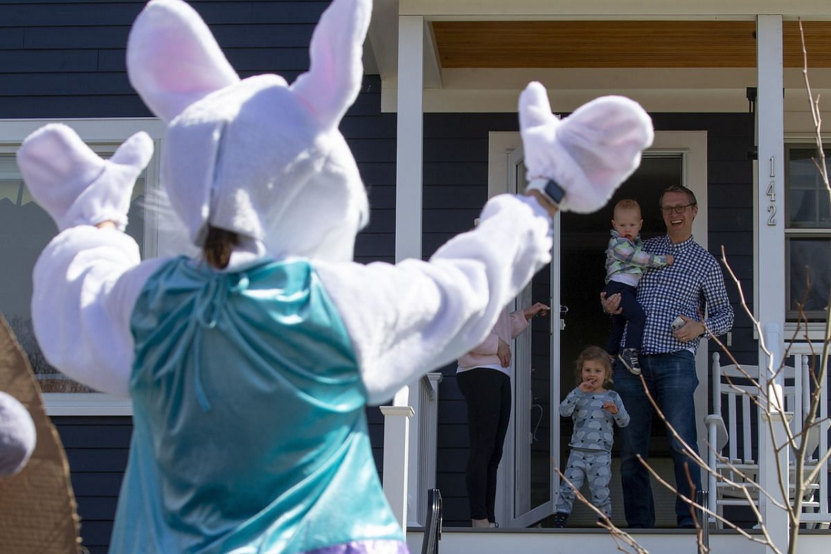 Claudia Frigerio, dressed in an Easter Bunny costume, waves to a family in Arlington, Massachusetts, on April 12, 2020. Realising that Easter would be different this year, Frigerio created a social media page inviting Arlington residents to request a