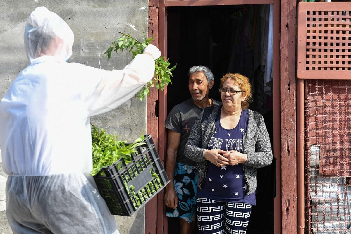 A Romanian Christian Orthodox priest wearing a protective hood distributes willow branches on April 12, 2020, after an Easter Sunday service held within closed doors due to the coronavirus pandemic.