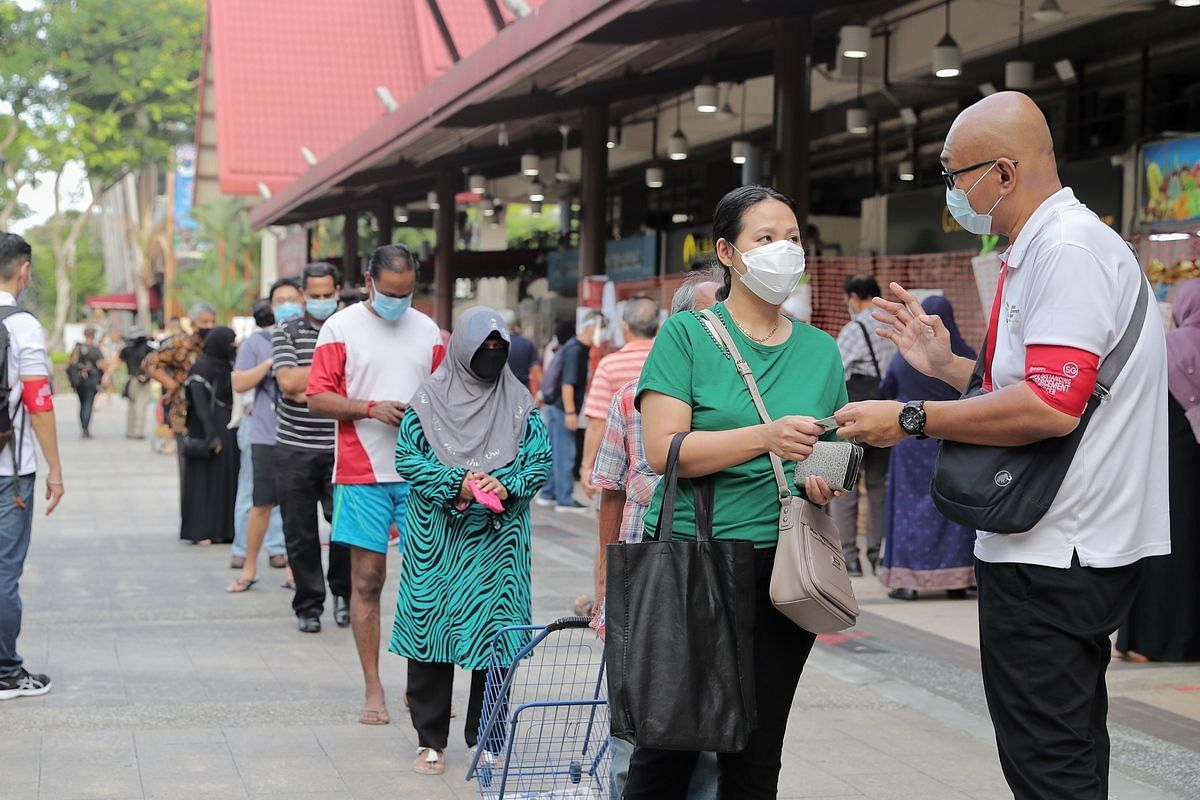 A safe distancing enforcement officer checks a shopper's identity card number as she queues to enter Geylang Serai market ahead of Ramadan this week, at 8am on April 22, 2020.
