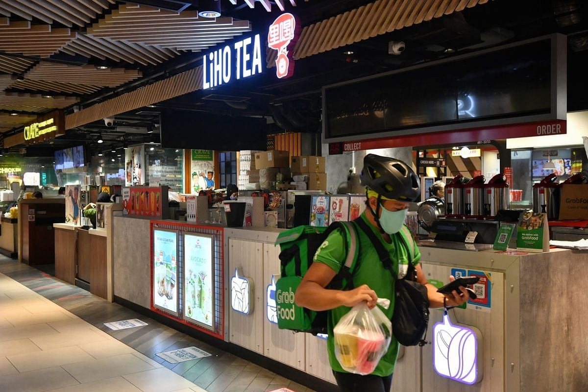 A Grab Food delivery rider holds drinks bought from a Crave outlet (left) that remains open as he walks past a closed LiHo counter at Clementi Mall on April 22, 2020.