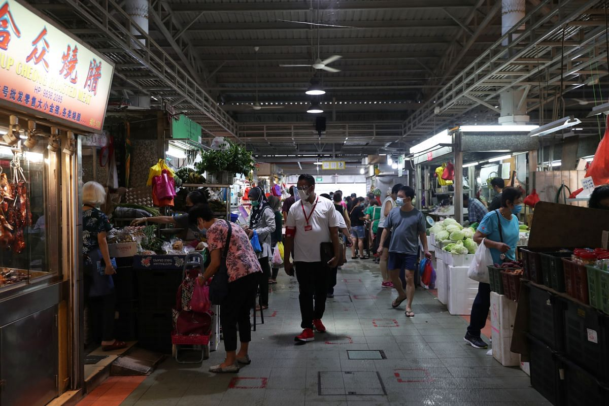 A safe distancing enforcement officer makes his rounds in the market at Block 505 Jurong West Street 52 on April 22, 2020.
