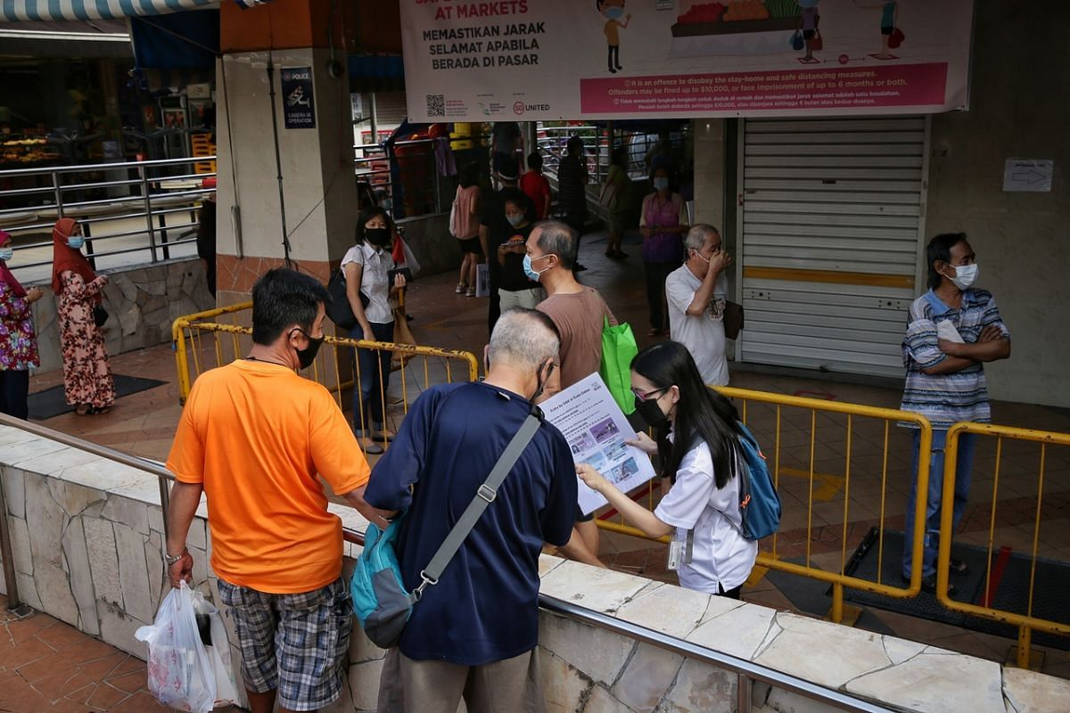 A safe distancing enforcement officer explains the new crowd control measures to patrons at Chong Pang Market on April 22, 2020.